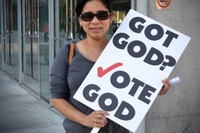 Mulher empunha cartaz: Ter Deus? Vote em Deus. Há países que tem partidos essencialmente religiosos